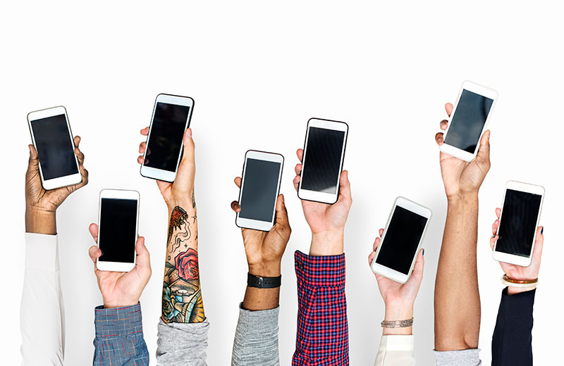 8 different people's hands holding smart phones up in the air